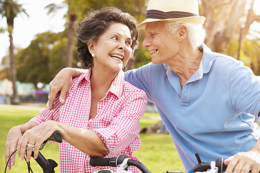Older man and woman outside in tropical climate. Man has arm around woman's shoulder.