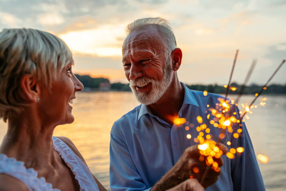 Mature couple on lake with sparklers