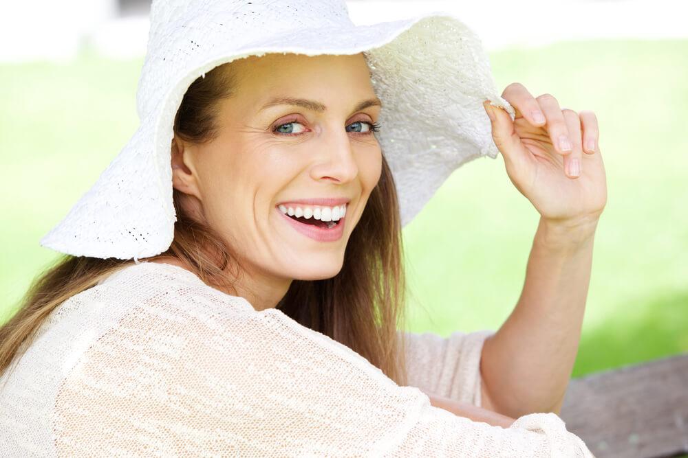 Older woman in floppy white hat smiling
