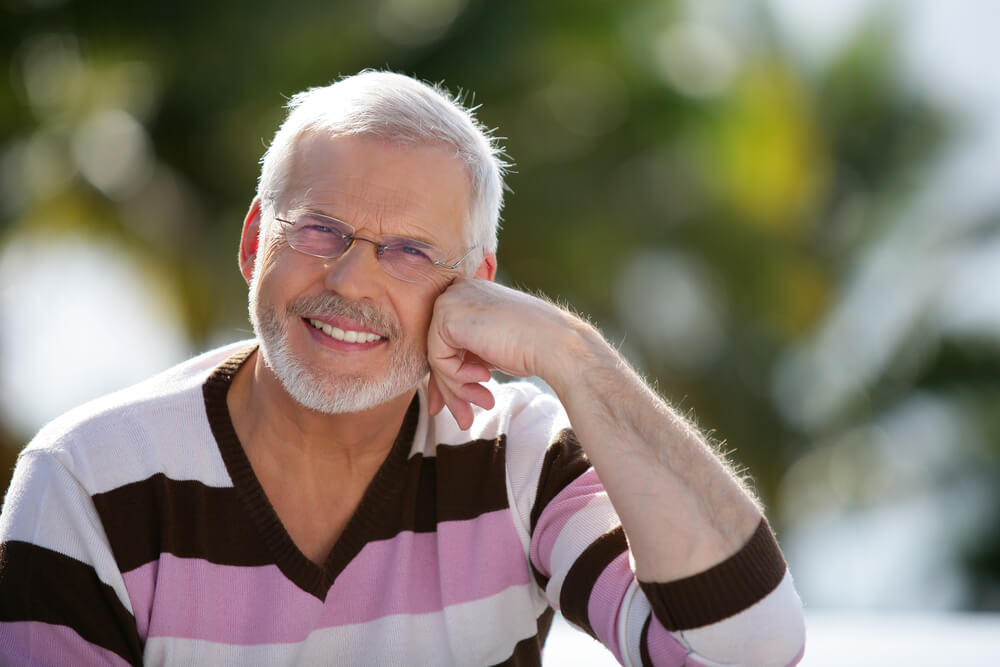 middle-age man smiling with hand to face