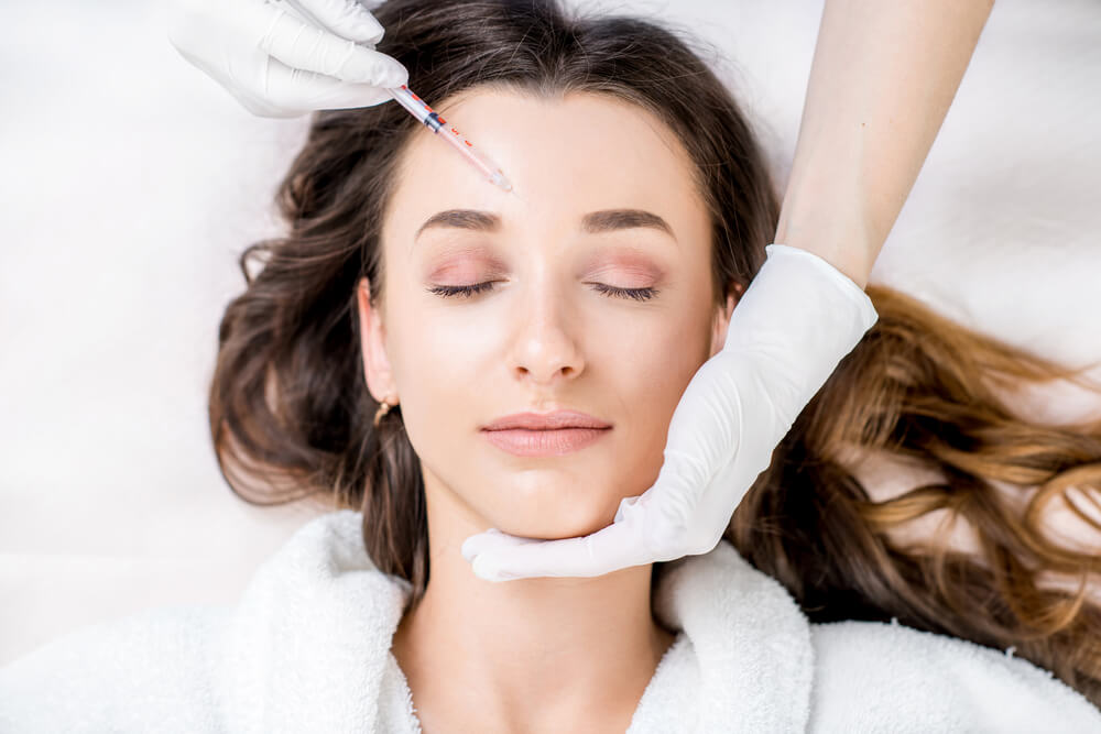 Young woman getting botox in forehead