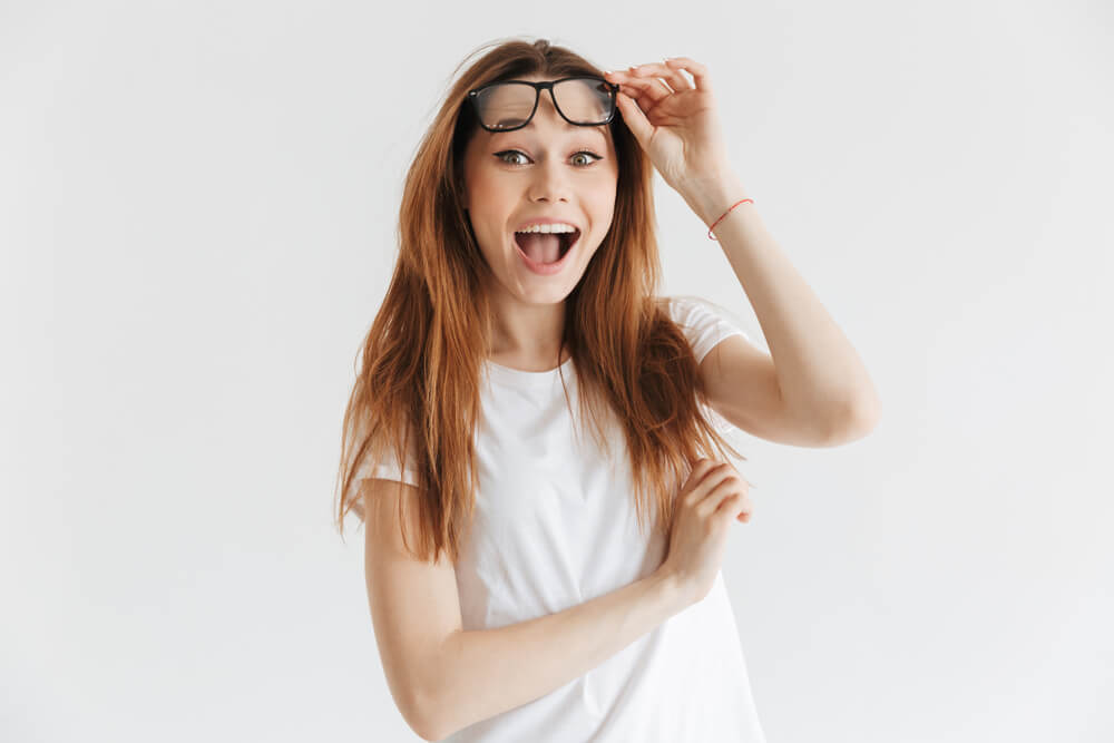 young woman looking surprised lifting up her glasses