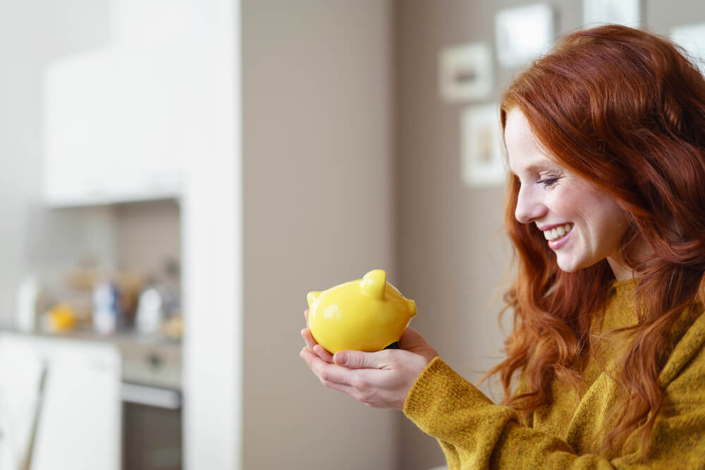 Woman with red hair looking at yellow piggy bank