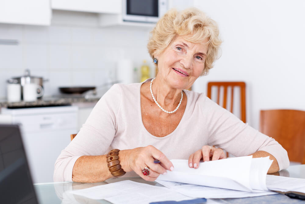 Older woman with paperwork on the kitchen table