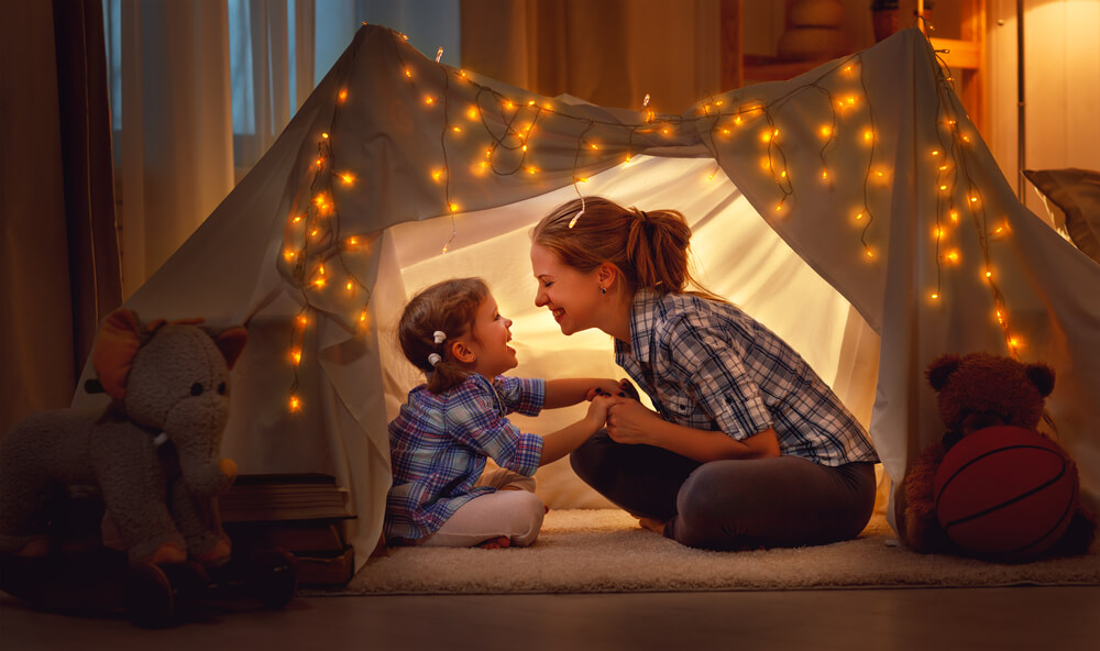 Woman and daughter in tent with lights