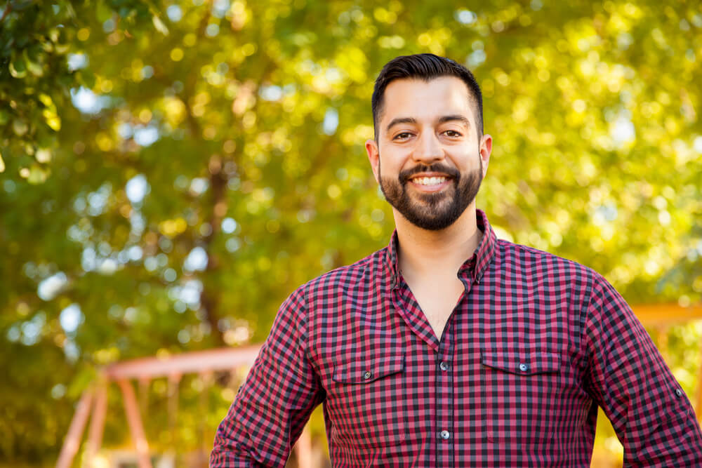 Young man in plaid shirt outdoors smiling
