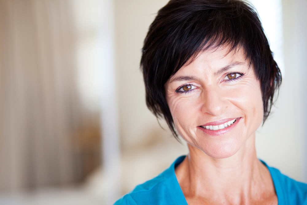 Mature woman with dark hair smiling