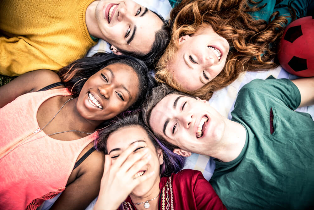 Group of teenagers looking up at camera and smiling